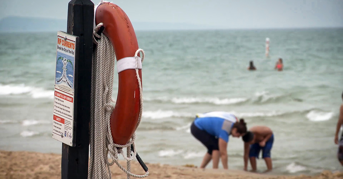 Signage about rip currents and emergency equipment at the Lake Michigan shoreline