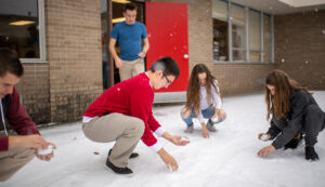 Students at Benzie Central run experiments on snow outside their school.
