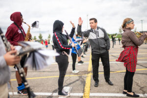 "Marching Mounties band director Bryan Mangiavellano, aka known as ""Mr. M,"" high-fives a clarinetist in the band"