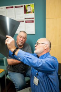 Dr. Philip Baty of Mercy Health Physician Partners in Rockford, Michigan and Howard Winchel look at an x-ray