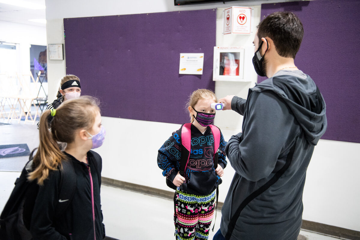 Young soccer players get a temperature check before practice