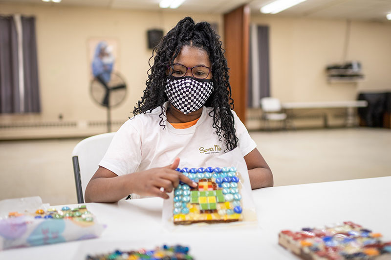 Maliyah Gladney, a seventh grader who has taken art and coding classes at Conant Avenue United Methodist Church, shows off a suncatcher that she made this year as part of an art course offered by Seven Mile, a University of Michigan student run organization that offers free after school music, art and coding lessons to kids in Detroit.