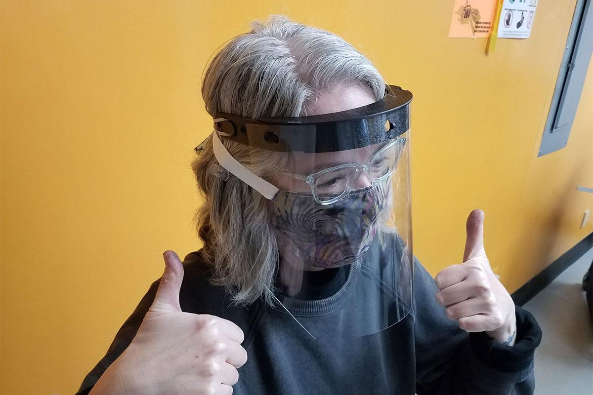 Pamela Cohen tests a face shield for fit at Maker Works.