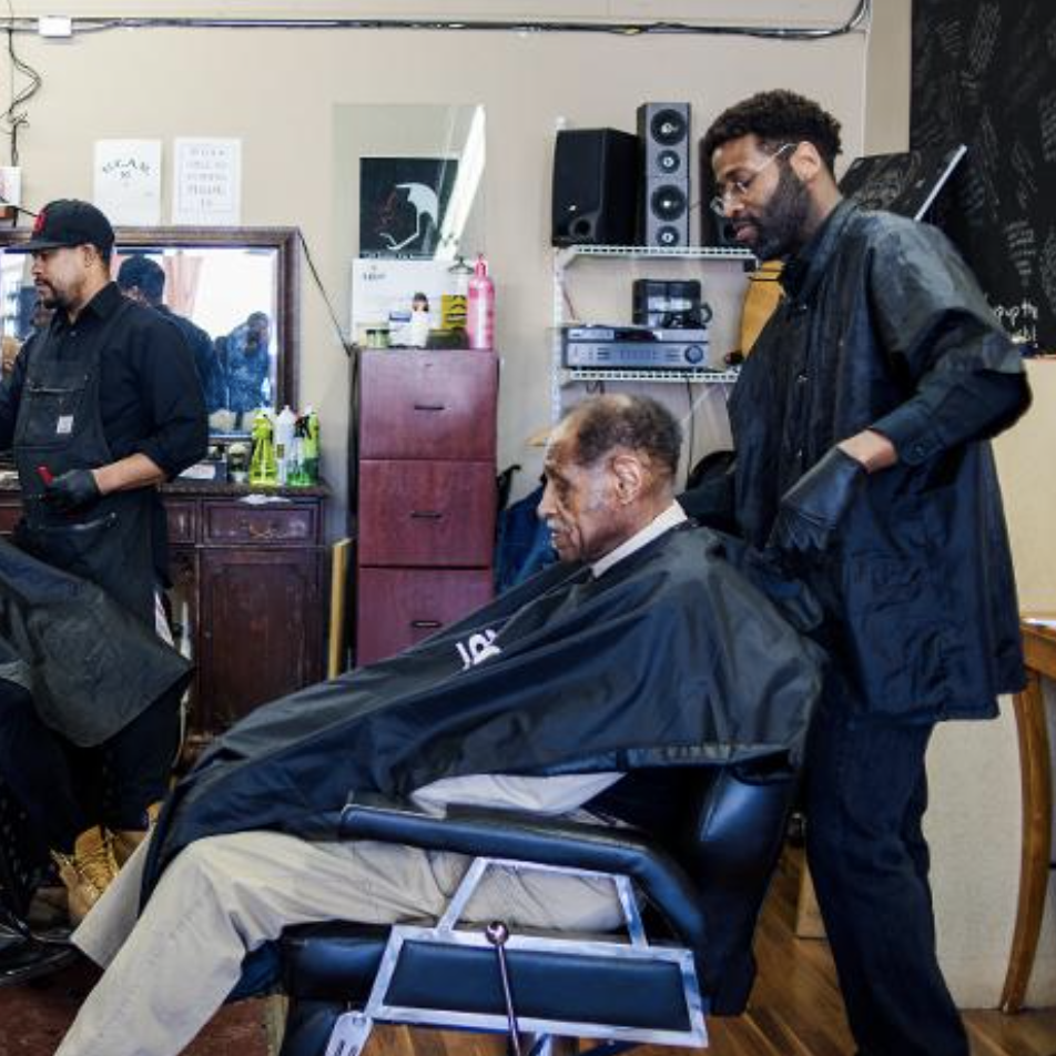 man getting haircut from another man