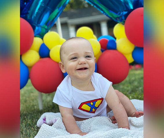 baby on lawn with colorful balloons