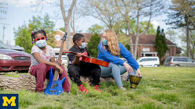 Siblings Chase (8) and Chelsey Singeltary (9) at Mission:City with their music teacher Samantha Redlich. In addition to teaching music classes, Redlich is the outgoing president of Seven Mile, a University of Michigan student run organization that offers free after school music, art and coding lessons to kids in Detroit. Photo by Eric Bronson/Michigan Photography.